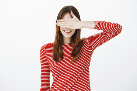 Portrait of playful adult female student in casual outfit, covering eyes with palm and smiling broadly, waiting permission to look at surprise, feeling temptation and happiness during birthday party 版權商用圖片