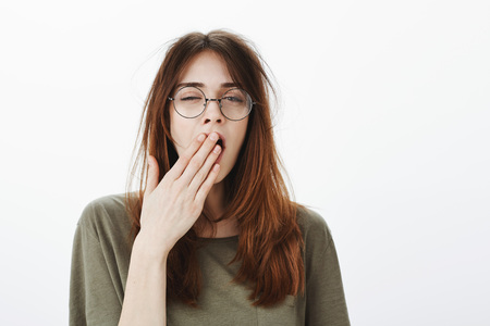 Shot of sleepy attractive caucasian woman with messy brown hair, wearing glasses, feeling tired after night without sleep, yawning, covering opened mouth with palm