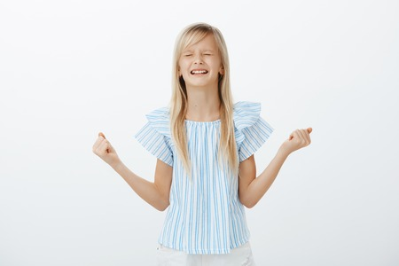 Offended little girl whining and crying, being disobedient. Displeased upset young daughter with blond hair, clenching spread fists and teeth, arguing wanting candy, standing over gray wall