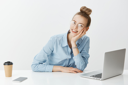 Girl sharing thoughts with coworker while sitting in office. Happy attractive woman in stylish outfit and glasses, leaning head on hand while sitting near smartphone and laptop, drinking cup of tea
