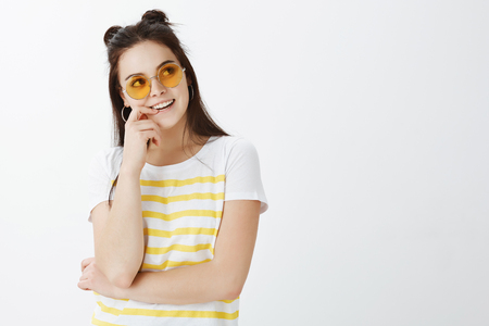 Waist-up shot of stylish creative young european female in trendy sunglasses, looking right with intrigued and joyful expression, smiling and biting fingernail while thinking and having idea in mind