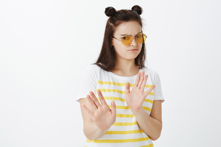 Displeased unhappy picky girlfriend in stylish clothes and t-shirt, tilting back and pulling palm in stop or enough gesture, rejecting offer, expressing disgust Stock Photo