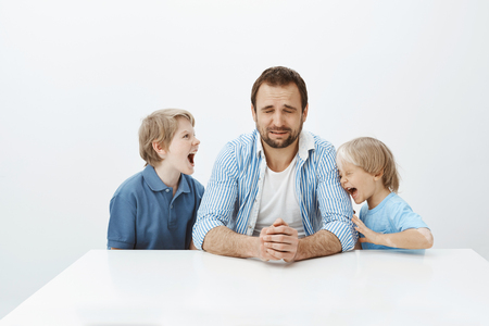 Father cannot deal with energetic sons with bad behaviour. Dad sitting at table and crying from desperate feelings while little boys are shouting and arguing, being depressed and miserable Stock Photo