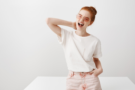 Portrait of stylish happy feminine woman in trendy sunglasses and outfit, tilting head, grimacing joyfully and winking flirty at camera, touching back of neck while standing and leaning on table Stock Photo