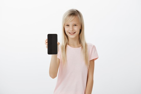 Studio shot of intrigued neat blond girl in pink t-shirt, smiling curiously and showing black smartphone at camera, asking brother password from device, wanting play games or brows in network