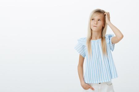 Amable chica adorable haciendo idea de cómo animar a mamá. Niño pequeño preocupado confundido con cabello rubio, rascándose la cabeza y mirando hacia arriba mientras piensa o planea el próximo paso, despistado e inconsciente Foto de archivo