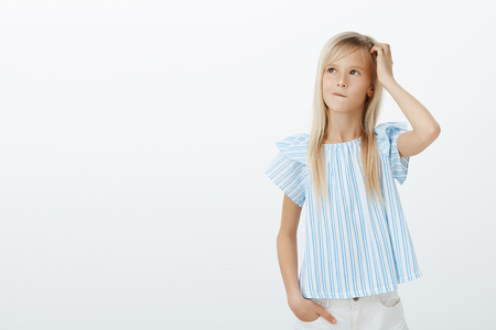 Freundliches entzückendes Mädchen, das Idee macht, wie man Mutter aufheitert. Verwirrt besorgtes kleines Kind mit hellem Haar, kratzendem Kopf und aufblickendem Denken oder Planen des nächsten Schrittes, ahnungslos und ahnungslos Standard-Bild