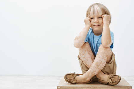 Cute little boy with blond hair and spots on skin, sitting with crossed feet, holding hands near face and smiling with joyful carefree expression, looking aside, feeling happy over grey wall