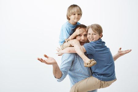 Questioned european father raising spread palms in clueless gesture, sticking out tongue and looking concerned at camera while son sitting on shoulders and touching forehead and kid hanging on chest