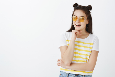 Creative dreamy and fashionable woman in sunglasses and yellow striped t-shirt, holding palm gently above chin and smiling joyfully while looking left, thinking or making decision over grey wall Stock Photo