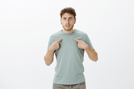 Studio shot of frustrated angry young man with bristle in t-shirt and earrings, pointing at himself and frowning, being insulted or offended by friend, standing outraged over gray wall