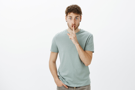 Portrait of displeased angry male teacher in casual t-shirt, lifting eyebrows from anger, saying shh while showing shush gesture and staring scary at camera, asking keep secret. Stock Photo