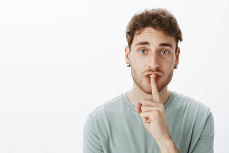 Close-up shot of confident handsome Caucasian guy with fair curly hair wearing earrings, saying shh while showing shush gesture with index finger over mouth, being serious over grey wall