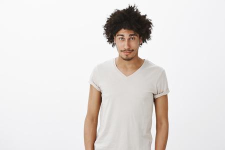 Studio shot of handsome hispanic guy with curly hair and fancy moustache gazing at camera while standing casually over gray background, wrinkling forehead from surprise or curiousity Stock Photo