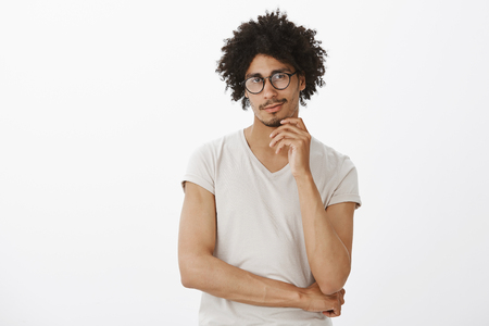 Portrait of intrigued charming hispanic guy in glasses and t-shirt, smirking and touching chin, gazing at camera with interest and curiousity, thinking or planning something over gray background