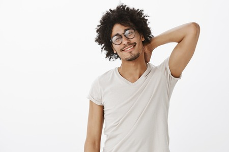 Studio shot of satisfied cute male in trendy glasses and casual t-shirt, touching back of neck and smiling while gazing at camera pleased expression, being proud of how he painted room himself