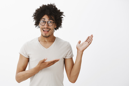 Portrait of happy excited attractive hispanic male hipster with moustache and afro haircut in glasses, pointing right with palms, showing something amazing and amusing, discussing interesting object Stock Photo