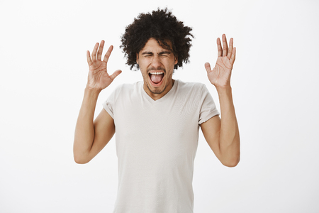 Portrait of irritated fed up and pissed mature male with moustache and afro haircut, raising palms near head, closing eyes and yelling, being pissed off while arguing, feeling pressure and stress Stock Photo