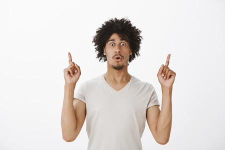 Amazed and surprised attractive guy with tanned skin and afro haircut, folding lips and gasping, gazing astonished at camera while pointing up with index fingers Stock Photo
