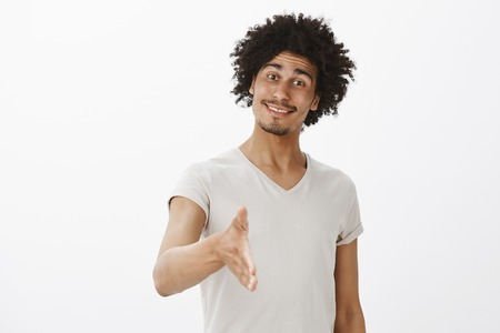 Optimistic happy cute male hipster with afro haircut and moustache, tilting head and smiling joyfully, pulling hand towards camera to give handshake and greet person