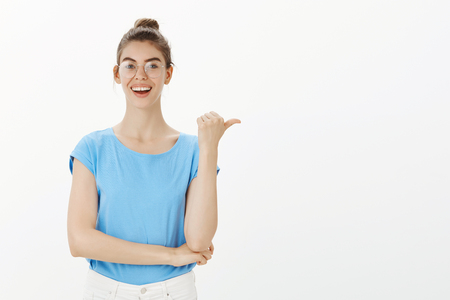 Meet my friend. Happy carefree european woman in bun and glasses, pointing right with thumb and smiling broadly, discussing interesting and positive news and directing at guy who involved in it