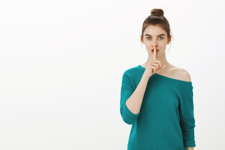 Shh, keep this secret from anyone. Portrait of feminine stylish woman in loose green sweater, showing shush gesture with index finger over mouth, folding lips, asking keep quiet or silence Stock Photo