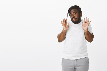 No way, I reject your offer. Careless plump africa-american male in white t-shirt, raising palms in surrender or no gesture, staring indifferent at camera, declining something over white wall