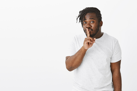 Flirty friendly african-american male with beard, making cute face while saying shh and showing shush gesture with index finger over mouth, keeping secrets or asking quiet, standing over white wall