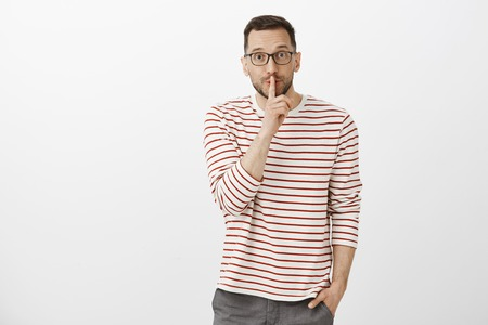 Portrait of creative good-looking adult male designer in striped shirt, asking keep secret, shushing and making shh gesture with index finger over mouth, being intrigued and happy over gray wall Stock Photo