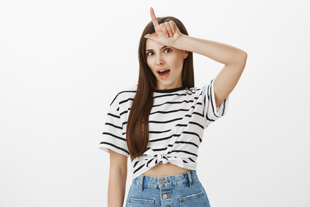 Portrait of popular attractive female student in striped t-shirt holding l word over forehead, mocking or laughing over rival who lost bet over white background