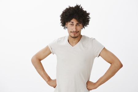 Portrait of curious intrigued attractive hispanic guy with tanned skin and afro haircut, lifting one eyebrow and holding hands on hips, standing over gray background and having something on mind