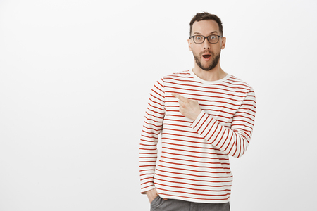 Portrait of amazed grinning mature husband in glasses, saying wow and pointing at upper left corner, being impressed with cool device, standing excited and satisfied over gray background