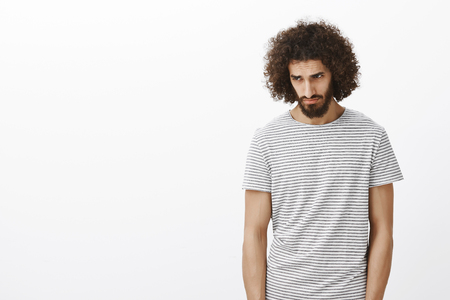 Gloomy desperate handsome male model in striped t-shirt, stooping head and looking down with sad look. giving up after losing, standing miserable over gray background with disbelief in own strengths