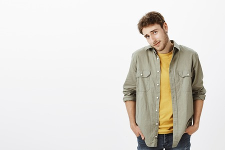 Portrait of handsome male model in shirt over t-shirt, tilting head and shrugging with hands in pockets, being unsure and doubtful