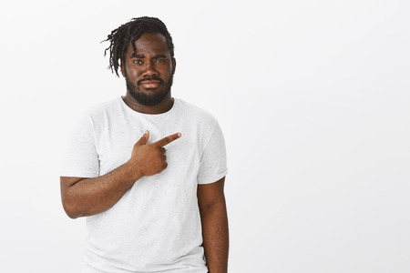Portrait of unimpressed displeased attractive dark-skinned guy in white t-shirt, pointing right, lifting on eyebrow and staring seriously at camera, being doubtful and suspicious Stockfoto