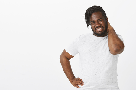 Studio shot of hesitating plump african-american male model with beard, holding hand on hip and scratching back of head with clenched teeth and displeased expression, being unsure or doubtful Stockfoto