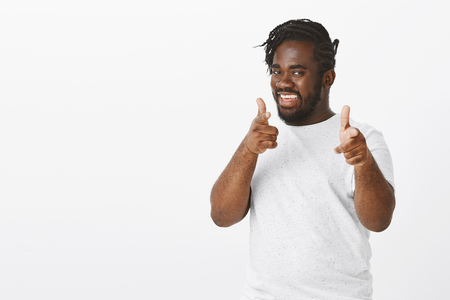 Friendly good-looking confident plump african-american in white t-shirt, smiling broadly and pointing with finger gun gestures at camera, having some intension or idea, greeting friends