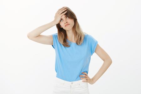 Portrait d'une jolie femme européenne fatiguée et agacée en t-shirt bleu, paupières roulantes, tenant la paume sur le front et la main sur la hanche, énervée ou épuisée