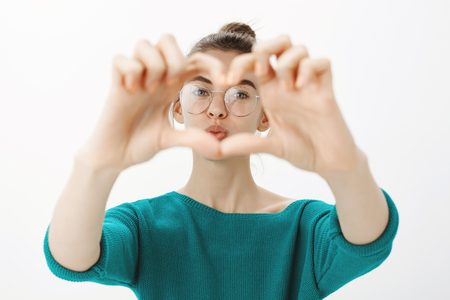 Close-up shot of emotive cute caucasian woman in glasses, pulling hands towards camera and zoom on heart gesture, gazing through hands and folding lips in air kiss, standing tender over grey wall