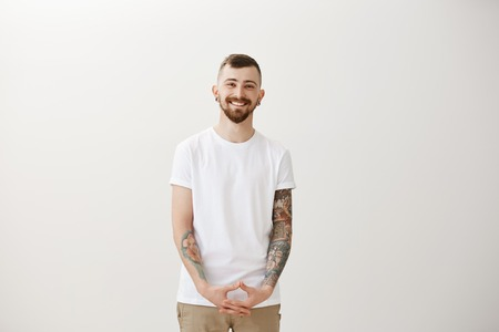 Studio shot of friendly happy young guy with beard and cool tattoos, holding hand in triangle over pants and smiling broadly, feeling unconfident while meeting new client, talking casually Stock Photo