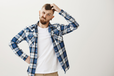 Intense male coworker trying solve issue, being clueless how to find solution. Frowning serious caucasian guy with beard, holding hand on hip and scratching head, trying to understand something