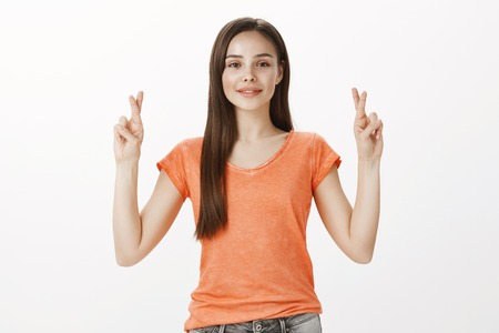 Girl praying her friend will win competition. Indoor shot of confident good-looking european woman in orange t-shirt, raising hands with crossed fingers, smiling broadly from happiness, wishing Stock Photo