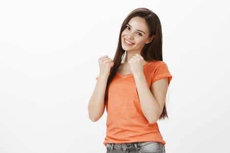 Girl wants show boxing moves she learnt. Portrait of attractive confident fit woman in casual clothes, raising clenched fists and smiling joyfully, being sportswoman and fighting over gray wall Banque d'images