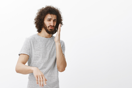 Displeased handsome mature hispanic man in striped t-shirt, waving palm near nose and frowning, smelling awful smell, being disgusted and disappointed in girlfriend cooking skills over gray wall