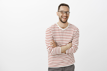 Portrait of timid good-looking european male with beard in glasses, crossing hands over chest and laughing out loud, feeling great while talking casually with new group of friends over gray background