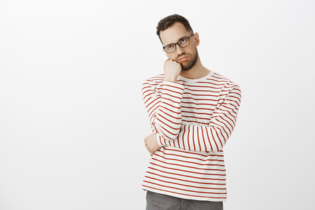 Guy hates how long boyfriend getting dressed. Portrait of tired and annoyed handsome european man in glasses, leaning head on fist and breathing out from boredom, standing unhappy over gray wall