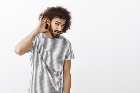 Whad did you say. Portrait of confused misheard attractive male student in striped t-shirt, holding palm near ear and turning at camera to hear better, looking from under forehead, waiting for answer