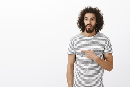 Amazed handsome musculine guy with beard and curly hair in trendy striped t-shirt, pointing right and teeling advice to girlfriend, standing assured over gray background, indicating at awesome place