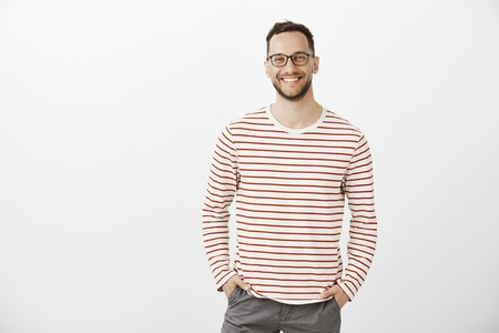 Portrait of confident friendly Caucasian employer in black glasses and striped pullover, holding hands in pockets and smiling cheerfully while greeting employees in office during casual meeting Фото со стока