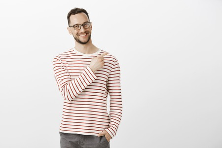 Portrat of proud confident aduly guy in glasses, holding hand in pocket and pointing at upper right corner with broad smile on face, being satisfied and joyful, feeling happy over gray background Reklamní fotografie